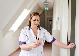 Zorgprofessional opent deur met mobile telefoon